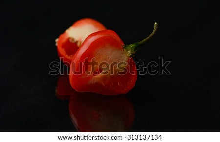 Super hot chilli cutted in half isolated over a black background - stock photo