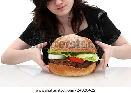 Super huge giant burger and teen girl trying to eat it. - stock photo
