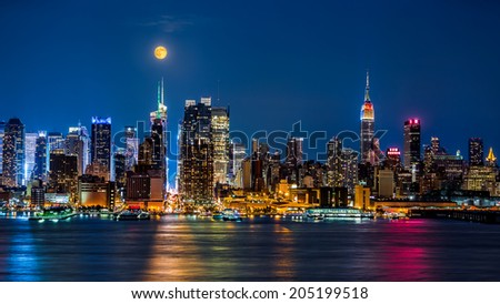 Super Moon above New York skyline. The top of the Empire State Building is illuminated with the colors of the German and Argentinian flags in honor of the Soccer World Cup final. - stock photo