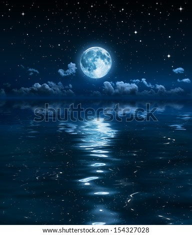 super moon and clouds in the night on sea  - stock photo