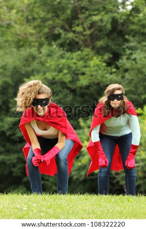 Super team of super hero girl with red cape and red gloves ready to attack - stock photo