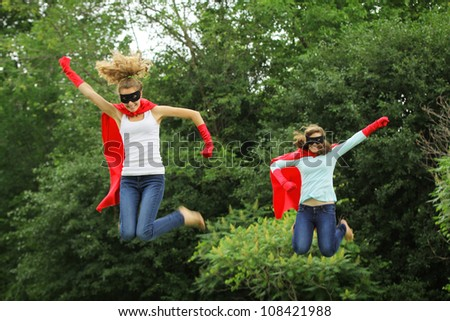 Super team of super hero girl with red cape, red gloves and black mask jumping in the air - stock photo