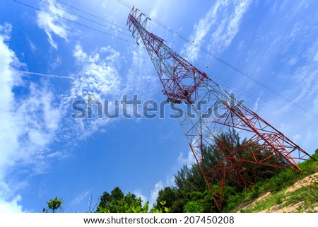 Super wide angle photograph of Electricity pylon with blue sky and white clouds, tilted horizon - stock photo