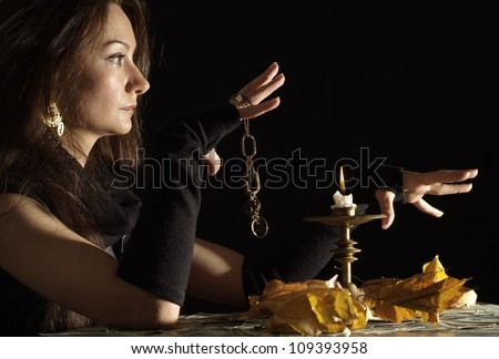 Superb girl as a witch on a dark background - stock photo