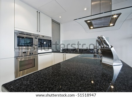 superb luxury kitchen with granite worktop and electric appliances - stock photo