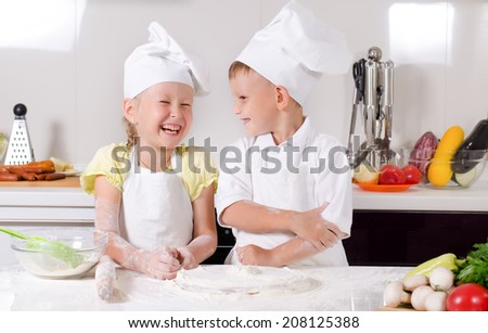 Supercilious little boy chef standing proudly with folded arms looking down on a cute little girl also in chefs uniform - stock photo