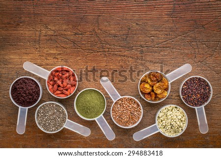 superfood abstract (wheatgrass, acai berry, goji berry, flax seed,chia seed,goldenberry,hemp seed, quinoa grain) - top view of measuring scoop against rustic wood with a copy space - stock photo