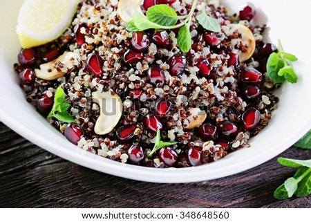 Superfood concept : Quinoa salad with pomegranate ,rosted nuts and mint on a rustic wooden table.Toned image .Selective focus. - stock photo