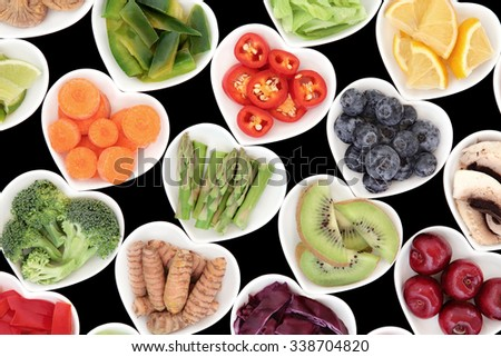 Superfood fruit and vegetable selection in heart shaped porcelain dishes over black background, high in vitamins and antioxidants. - stock photo