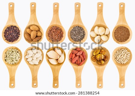 superfood grain, seed, berry, nuts and garlic abstract - top view of isolated on white wooden spoons (two rows) - stock photo