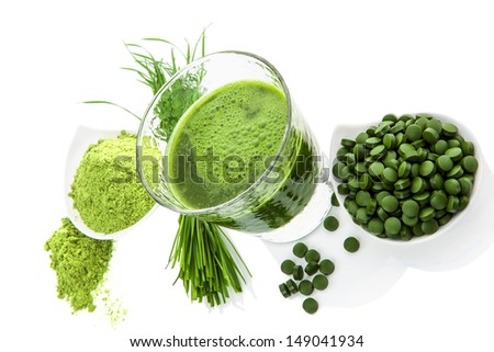 Superfood. Ground wheatgrass, barley grass blades, chlorella pills and spirulina green juice isolated on white background.  - stock photo