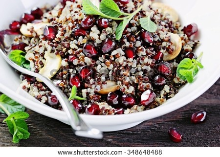 Superfoods concept : Quinoa salad with chickpeas,pomegranate and mint on a rustic wooden table.Toned image .Selective focus. - stock photo
