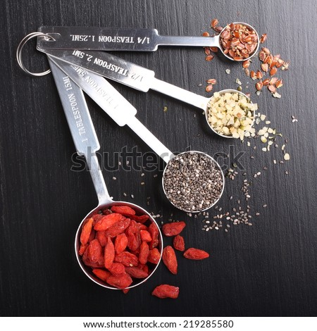 Superfoods. Goji berries, chia seeds, hemp seeds and broken flax seeds in metal measuring spoons - stock photo