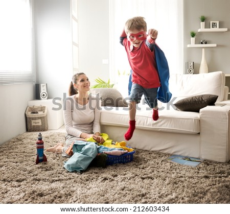 Superhero boy and his mother doing laundry together in the living room. - stock photo