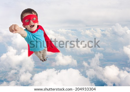 superhero boy child flying mid air above cloud level - stock photo