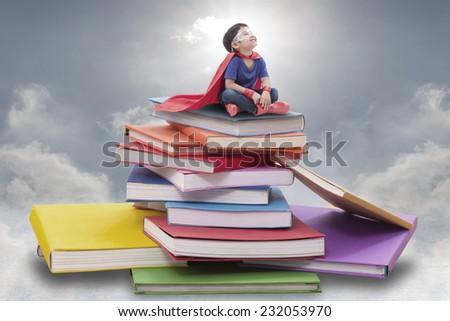 Superhero boy child sitting on pile of books  - stock photo