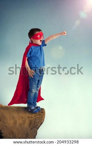 superhero boy child standing on a cliff edge - stock photo