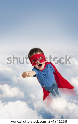 superhero boy flying in the sky through clouds - stock photo