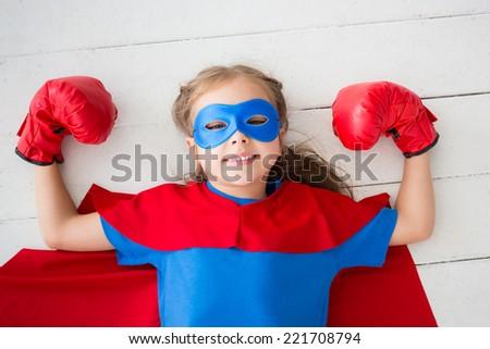 Superhero child lying on floor at home - stock photo