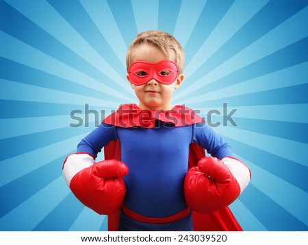 Superhero child with boxing gloves concept for childhood, imagination, aspirations and strength - stock photo
