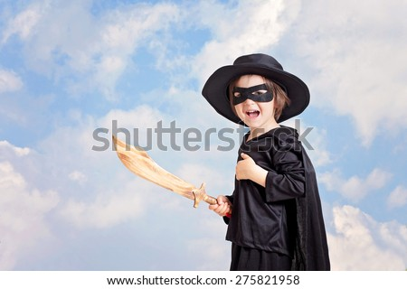 Superhero child with sword and costume on a blue sky background, smiling at the camera - stock photo