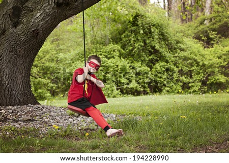 Superhero fun!  Adorable little boy dressed in a superhero costume and playing on his swing.