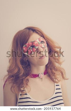 Superhero girl wearing mask with strawberries, looking away - stock photo