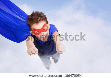 Superhero kid against blue sky background - stock photo