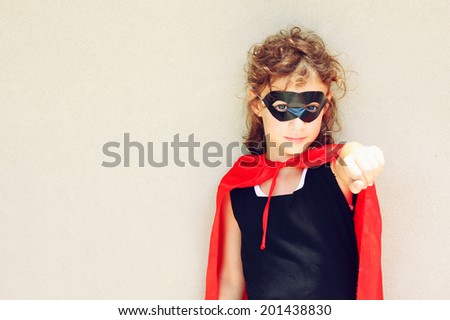 Superhero kid against textured wall background. photographed outdoors under natural light during playing activity  - stock photo