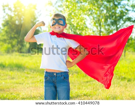 Superhero Kid Showing his Muscles over nature background. Little boy wearing superhero costume and having fun outdoors - stock photo
