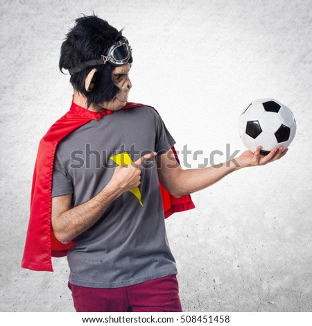 Superhero monkey man holding a soccer ball on textured background