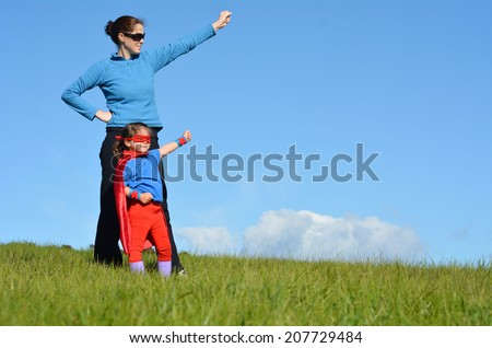 Superhero mother and daughter against dramatic blue sky background with copy space. concept photo of Super hero, girl power, play pretend, childhood, imagination. - stock photo