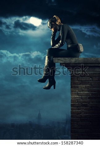 Superhero thoughtful sitting on the roof of a building - stock photo