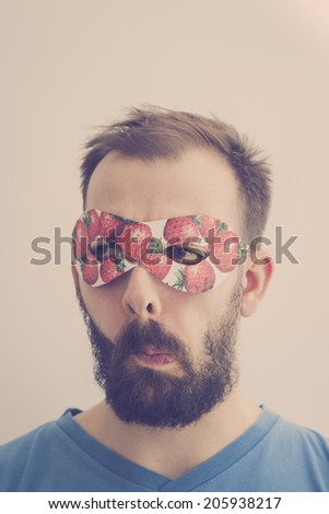 Superhero wearing mask with strawberries, making silly faces. Retro colors