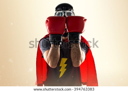 Superhero with boxing gloves covering his face over ocher background