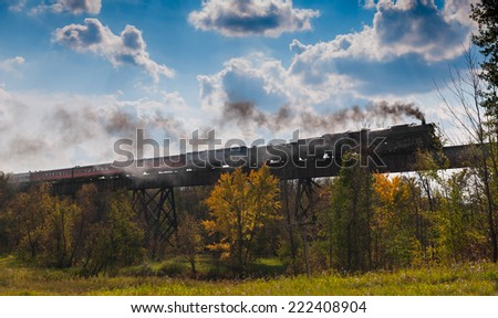 SUPERIOR, WI - SEPTEMBER 27: Fall colors tour of the Milwaukee Road #261 Steam Engine from Minneapolis, MN to Duluth, MN. Train crosses the Nemidji River Trestle on September 27 2014 near Superior WI - stock photo