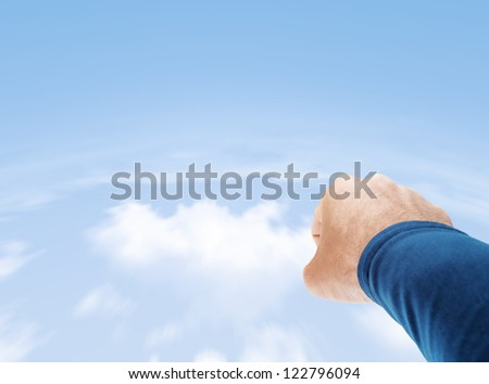 Superman hand flying in cloudy sky with copy space - stock photo