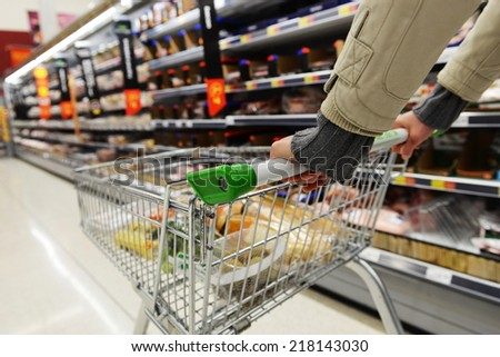 Supermarket Aisle View of a Shopping Trolley and Shelves - Image has a Shallow Depth of Field - stock photo