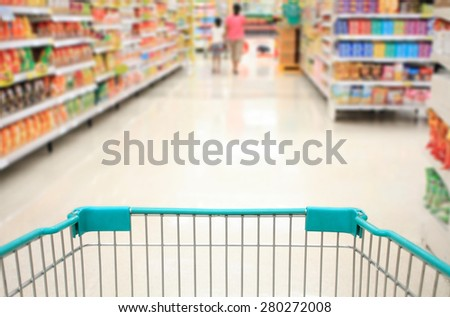 supermarket aisle with shopping cart  - stock photo