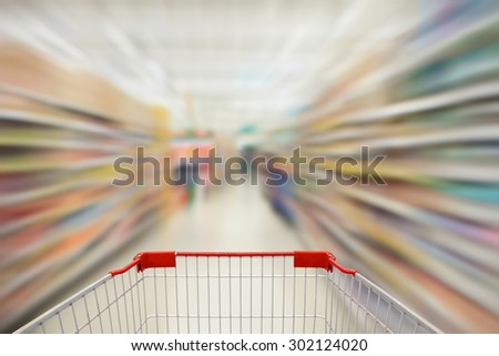 supermarket aisle with shopping cart in motion - stock photo