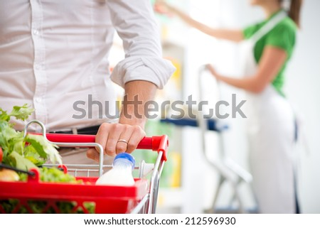 Supermarket customer's hand close-up with sales clerk on background. - stock photo