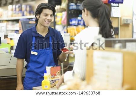 Supermarket employee in blue apron assisting female customer - stock photo