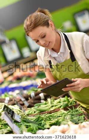 Supermarket employee putting vegetables in shelves