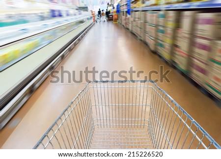 Supermarket interior, empty red shopping cart.  - stock photo