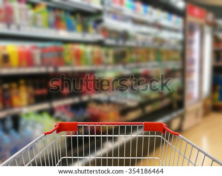 Supermarket interior with empty shopping cart - stock photo