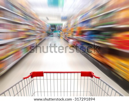 supermarket shelves aisle blurred background with shopping cart in motion - stock photo
