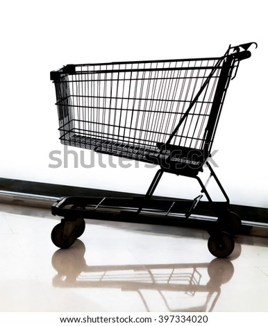 Supermarket shopping cart stay on white glass wall background.