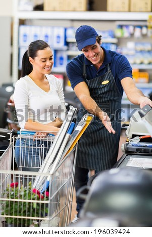 supermarket worker help female customer in buying bbq grill - stock photo