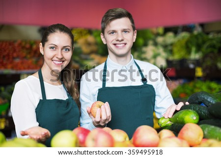 Supermarket workers arranging apples on display and smiling - stock photo