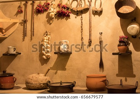 Supersano, Italy - May 24, 2017: Old kitchen utensils hanging on the wall lit by a dim light of the old farmhouse